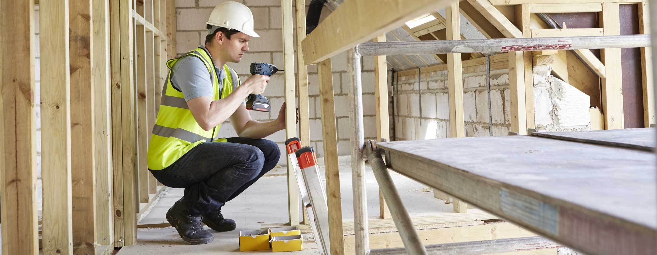 Man in construction uniform using a drill to construct the interior of a home or business.